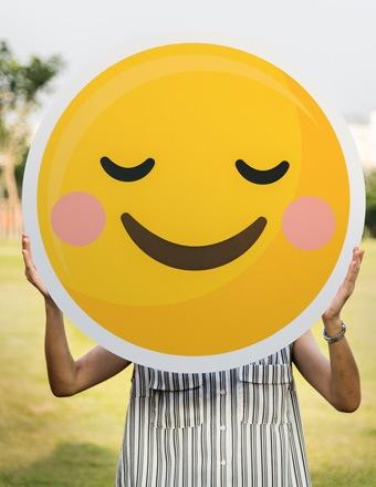 Femme portant un énorme emoji qui sourit devant son visage